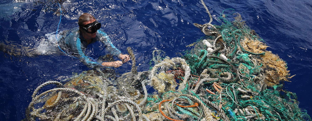 Image of Emily Penn attaching GPS tracker to ghost nets